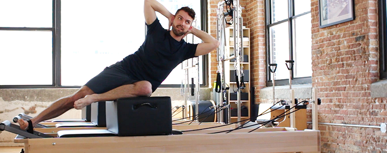 Photo of a man working out on a Studio Reformer with a Sitting Box