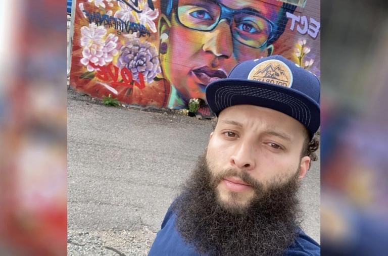 Elijah McKnight, posing for a selfie in front of a mural of Elijah McClain.