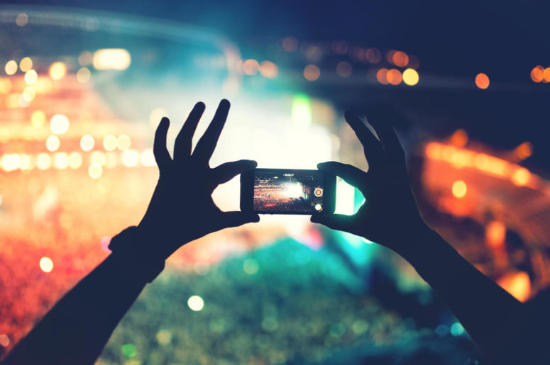 Silhouette of hands using camera phone to take pictures and videos at pop concert, festival