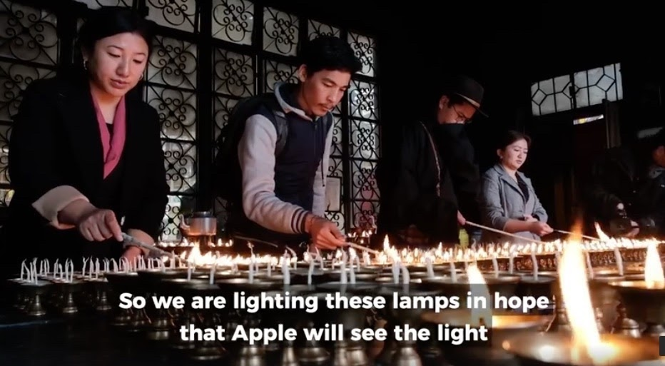 four people lighting butter lamps in a monastery in dharmsala with the captions we are lighting these lamps in hope that apple will see the light