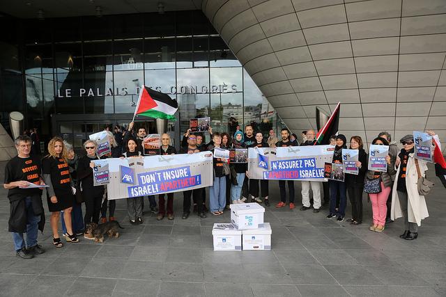 Photo de groupe lors de la mobilisation devant l'Assemblée Générale des Actionnaires d'AXA. Sont rassemblés une vingtaine de militants SumOfUs et du mouvement BDS avec des banderoles et des pancartes.