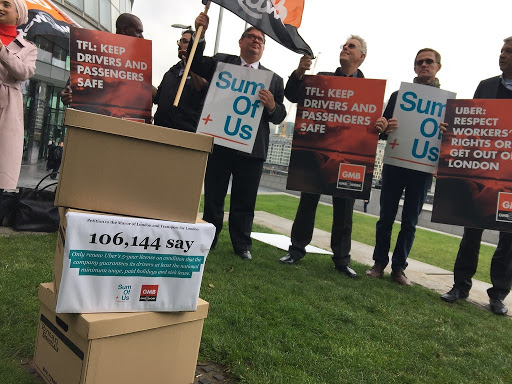 Group of Uber drivers and SumOfUs campaigners stand in front of a printed copy of 100,000 petition signatures
