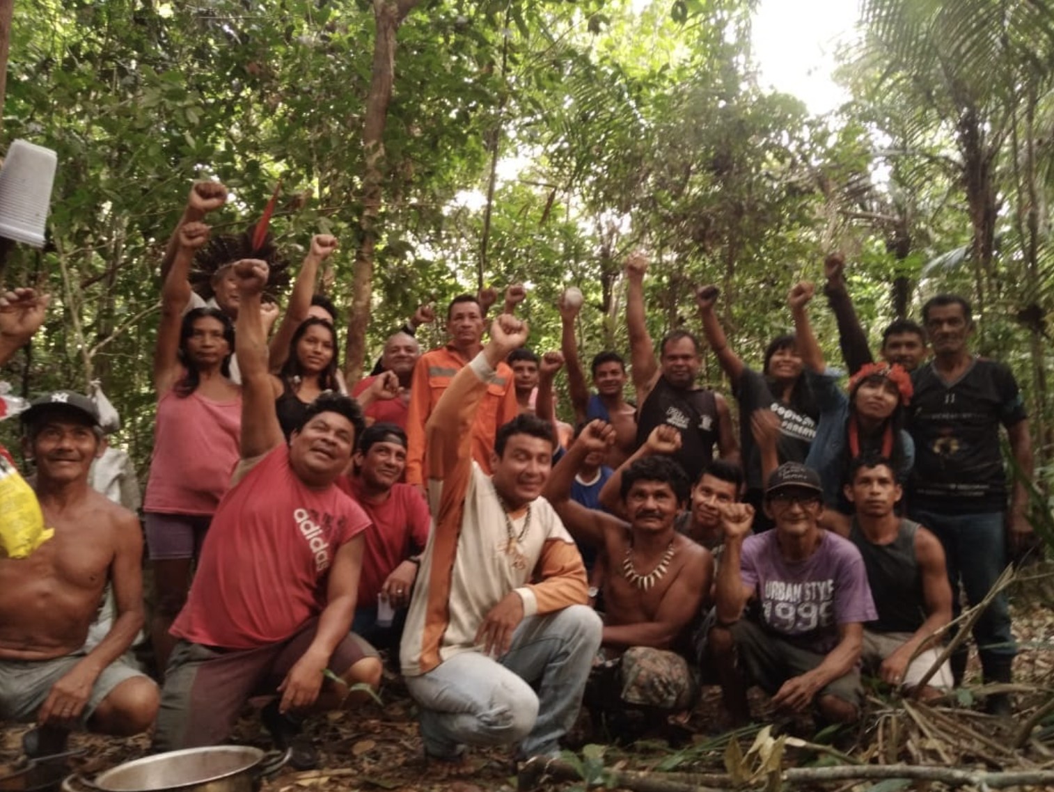 A group of Tupinambá community members kneeling and standing for a group photo in the forest all raising their right fists in solidarity