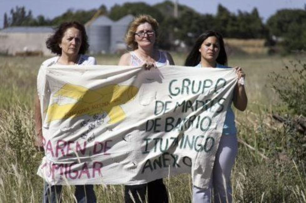 Group of mothers in a field holding a sign calling for action on glyphosate poisoning.