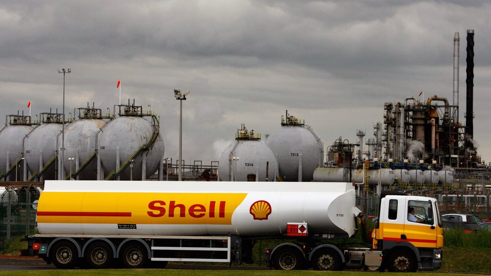A Shell oil truck passes in front of an oil refinery