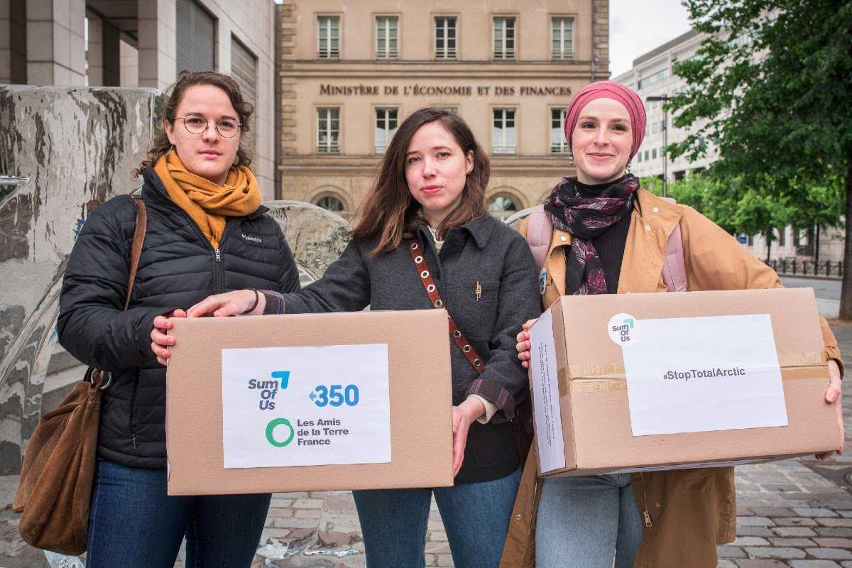Photos of the three campaigners in front of the Ministry carrying the boxes containing the 200,000 signatures