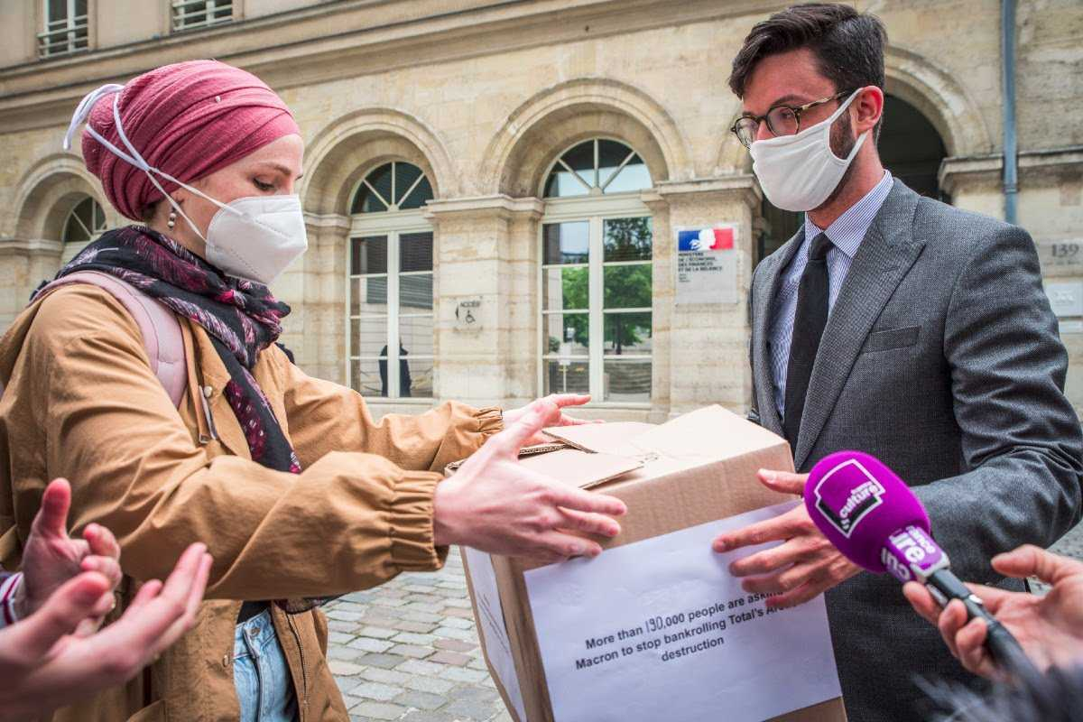 Photo of the delivery of your signatures by our campaigner,...  Leyla, to Nicolas Dufaud, Chief of Staff of the Ministry of the Economy and Finance