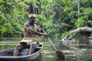 Indigenous man rowing in a canoe in the Amazon Rainforest in Brazil
