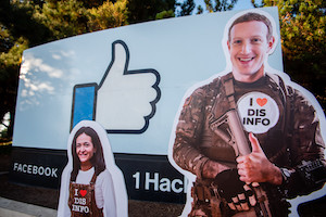"""""""Mark Zuckerberg with an I heart DisInfo pin in front of the Facebook Headquarters sign"""