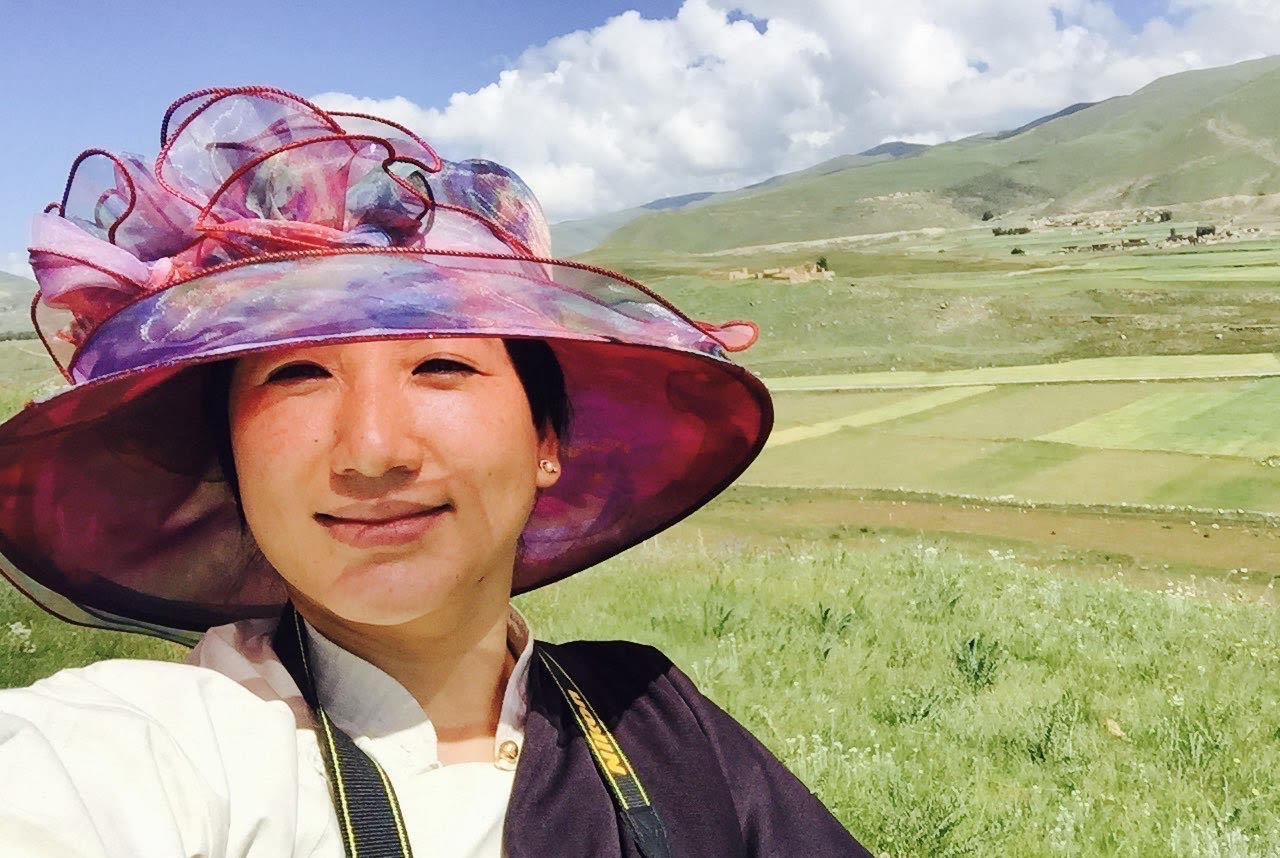 image of a woman called Lobsang Yangtso in a field wearing a hat