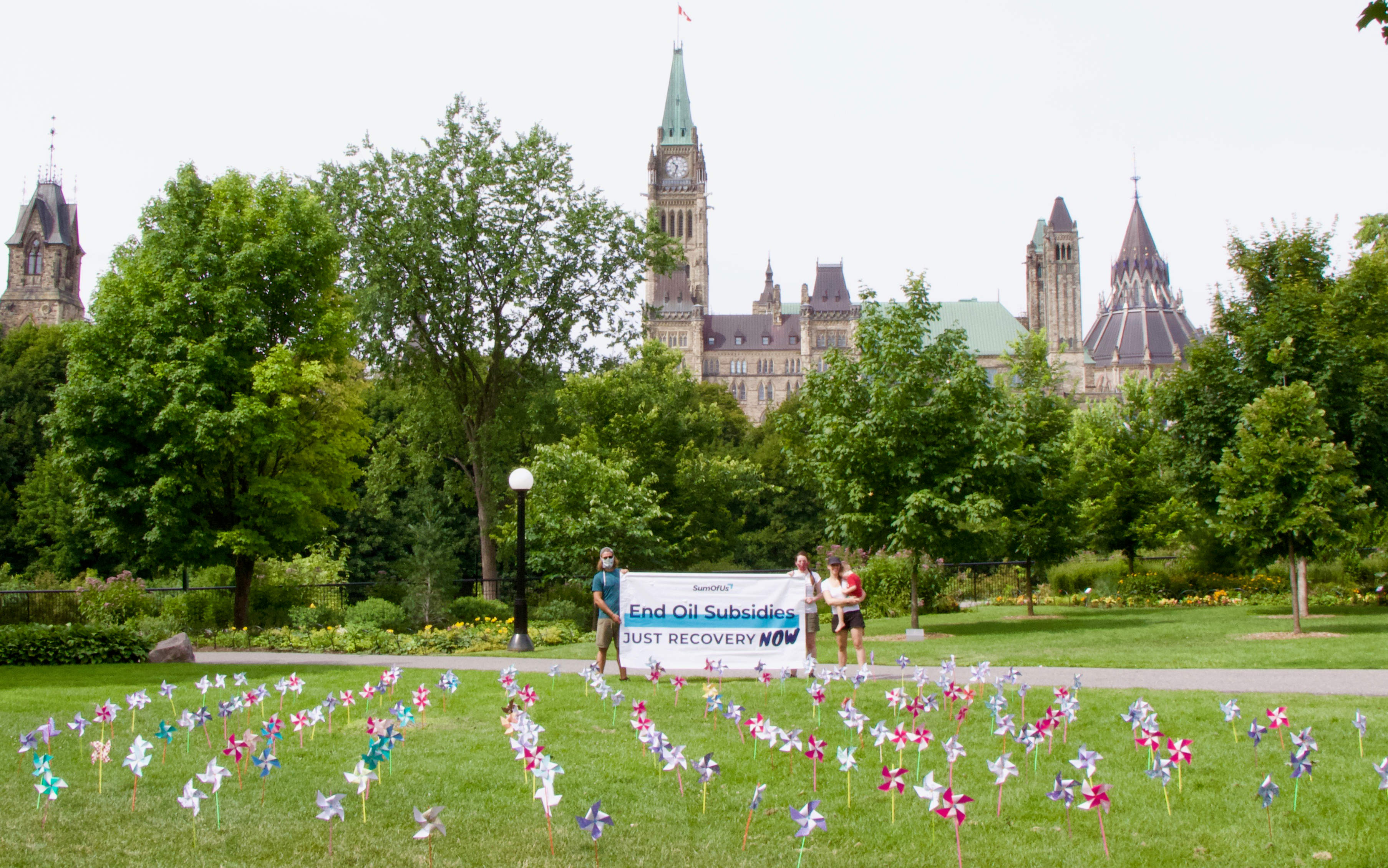 Windmills on the lawn with banner outside Parliament Hill
