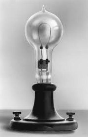 Thomas Edison uses a light bulb to light a lamp.