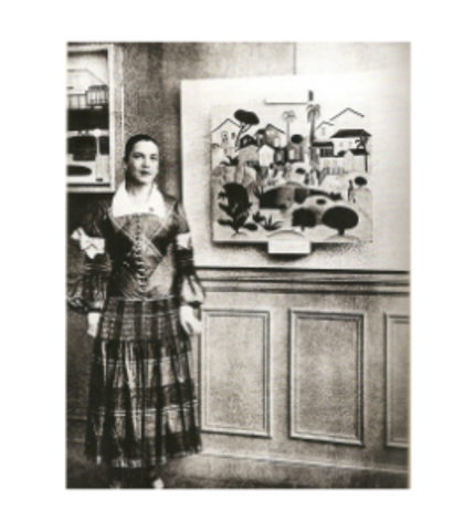Picture of Tarsila's First Solo Exhibition in Paris.  She's attired in a marvelous dress from fashion designer Paul Poiret, and standing next to her painting Morro da Favela (Hill of the Favela)