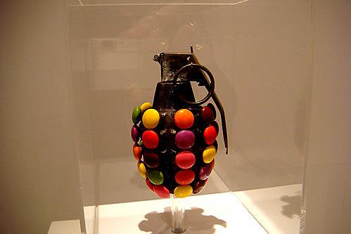 "Prof - La vitrine / Kata Legrady: ""Pineapple Sculpture (Blue, Brown, Green, Orange, Pink, Purple, Red, Yellow)"" (Sculpture. Grenade à gragementation recouverte de Smarties, dans une vitrine en plexiglas. 25 x 15 x 15 cm. Galerie Pékin Fine Arts, Chine)"