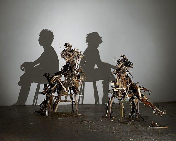 """Prof - La projection / Tim Noble et Sue Webster: """"WILD MOOD SWINGS (Changements d'humeur brutaux)"""" (Installation lumineuse + autoportraits. 2 escabeaux en bois, bois et projecteur lumineux. Tim: 178.5 x 110 x 167 cm. Sue: 215 x 98.5 x 130 cm)"""
