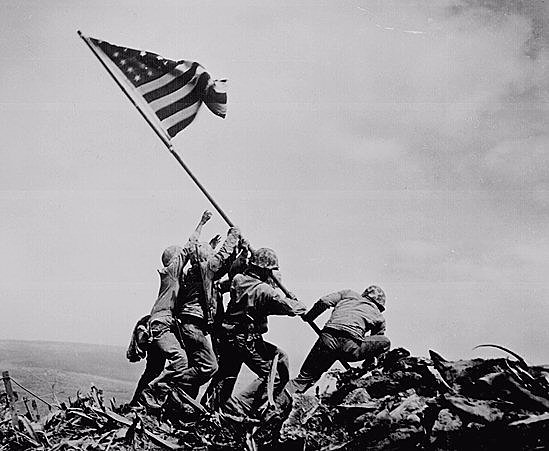 Five Marines and a Navy raising the American flag