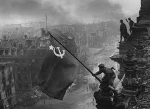 soldiers rose a Soviet flag on top of the Reichstagg