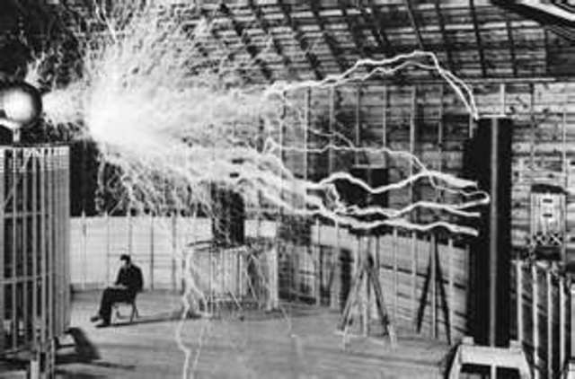 Nikola Tesla makes a device to produce and transmit high-frequency electricity