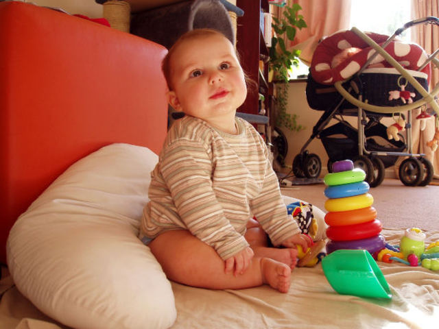 A baby can hold its head up and reach for objects.
