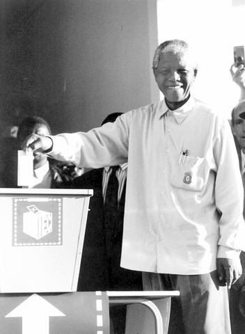 Mandela votes for the first time in South Africa's first democratic election.
