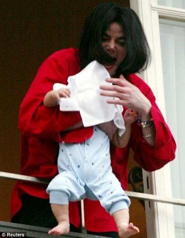 Dangles his newborn son, Prince Michael II.