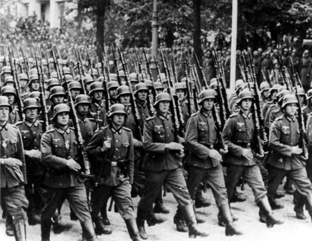 Reintroduces the draft and rearms Germany (violates Treaty of Versailles)