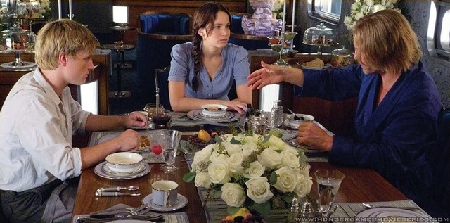 Katniss and Peeta meet Haymitch, their mentor, on the train.