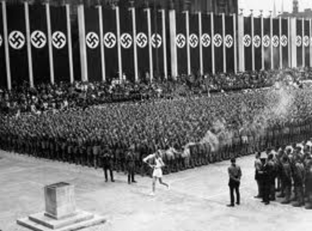 """The Olympic Games take place in Berlin. Anti-Jewish signs (i.e., """"Jews Not Welcome"""") are removed until the Games are completed"""