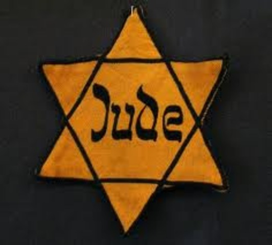 Germans force Jews in Poland to wear a yellow Star of David on their chests or a blue-and-white Star of David armband.