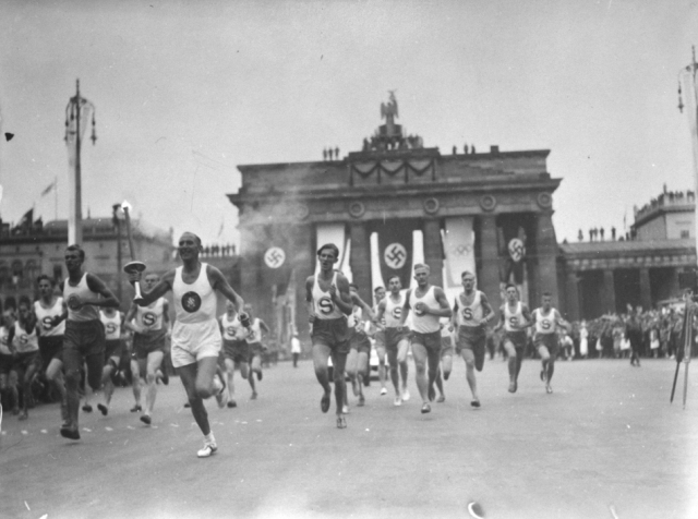 """The Olympic Games take place in Berlin. Anti-Jewish signs (i.e., """"Jews Not Welcome"""") are removed until the Games are completed."""