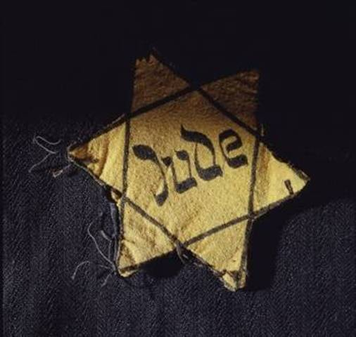 Germans force Jews in Poland to wear a yellow Star of David on their chests or a blue-and-white Star of David armband