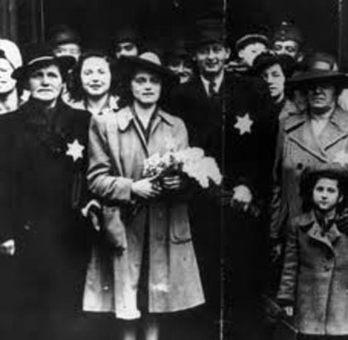 """German Jews above the age of six are forced to wear a yellow Star of David sewed on the left side of their clothes with the word """"Jude"""" printed in black."""