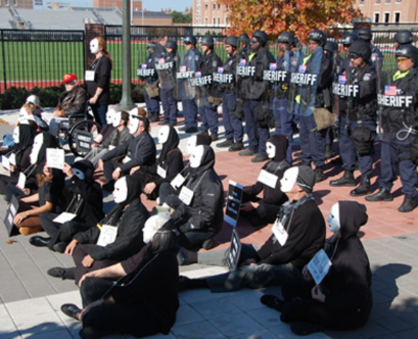 Masked Protesters Sit Outside Moody Coliseum