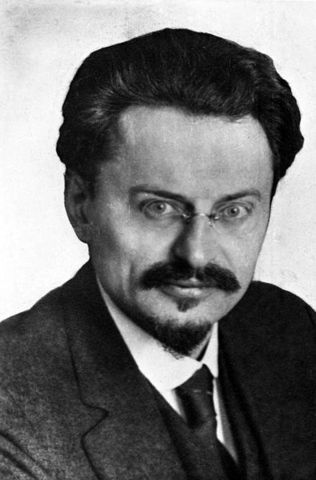 The new Russian gov't, represented by Trotsky and under orders from Lenin, sign the Treaty of Brest-Litovsk