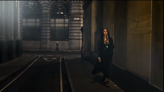 The wide shot further depicts the cittyscape setting and gives the viewer a full view of her costume; a black hoodie and black jeans suit the night time look of the video