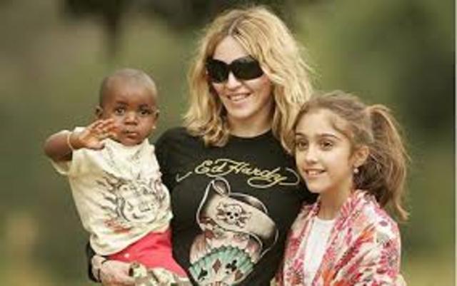 Madonna adopts two children.