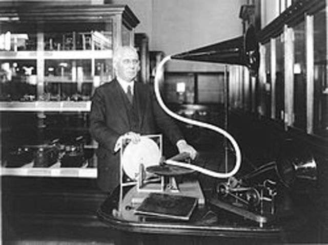 "- Emile Berliner invents the flat record player (""gramophone"") using acoustic horn            and licenses technology to record companies who make ""70-rpm"" disks"