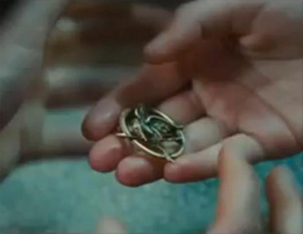 Madge gives Katniss the mockingjay pin