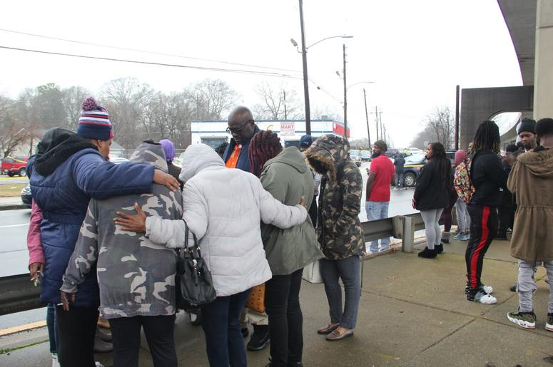 A circle of prayer is held across from the auto sales business where the bodies of 2 men were found inside a vehicle Thursday morning
