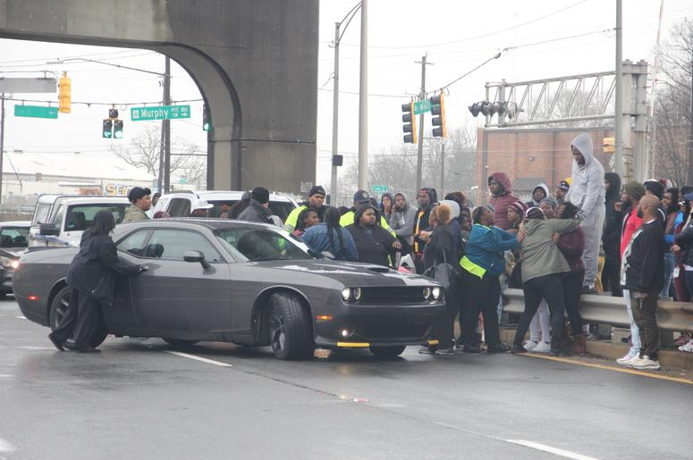 Onlookers surround a vehicle that police had allowed to leave the scene where 2 men were found dead inside a vehicle