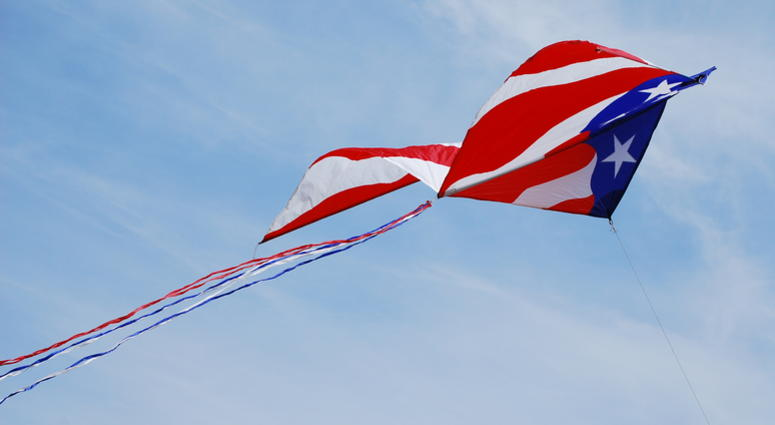 A kite with a Stars and Stripes theme, trailing red white and blue tail streamers soars diagonally across the frame, giving a sense of speed and movement.