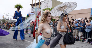 Parade attendees in costume walk down Surf Avenue during the 35th Annual Mermaid Parade: Coney Island USA at Coney Island in the New York City borough of Brooklyn New York, NY, on June 17, 2017.