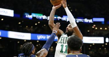 Boston Celtics guard Kyrie Irving shoots over Indiana Pacers guard Wesley Matthews and forward Thaddeus Young