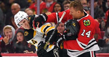 Boston Bruins defenseman Rob O'Gara (44) and Chicago Blackhawks right wing Richard Panik (14) fight during the second period at United Center.