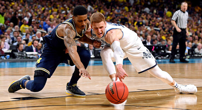 Michigan Wolverines guard Charles Matthews and Villanova Wildcats guard Donte DiVincenzo go for a loose ball during the national championship game on April 2, 2018, at the Alamodome in San Antonio.