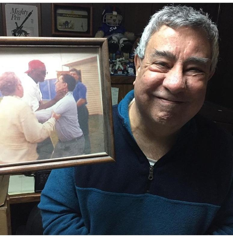Ernie Palladino poses with a photo of Lawrence Taylor choking him.
