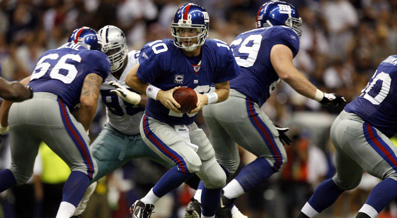 The Giants' Eli Manning prepares to hand off the ball against the Dallas Cowboys at Texas Stadium on Sept. 9, 2007.