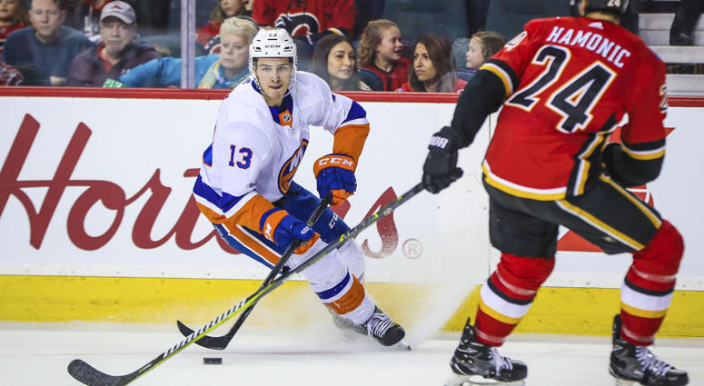 Islanders center Mat Barzal (13) controls the puck against the Flames on March 11, 2018, at Scotiabank Saddledome in Calgary.
