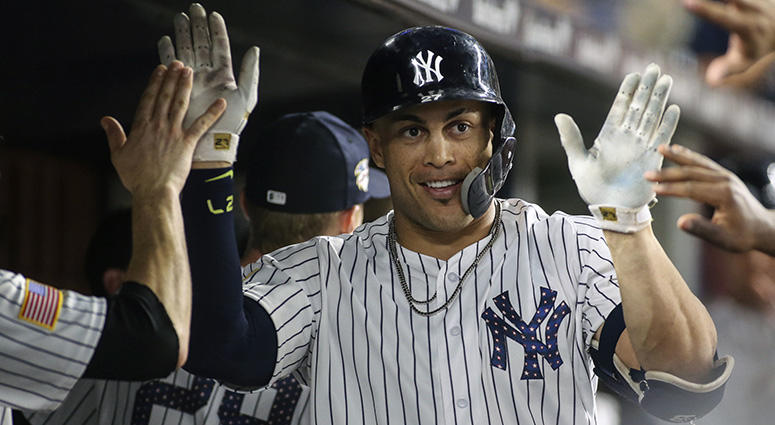 New York Yankees right fielder Giancarlo Stanton (27) is congratulated after hitting a home run in the eighth inning against the Atlanta Braves at Yankee Stadium on Jul 3, 2018.