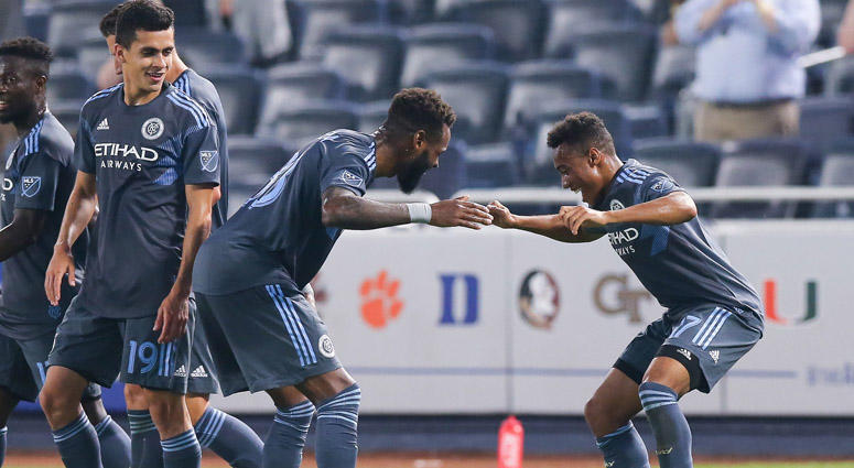 NYCFC's Jonathan Lewis (right) celebrates with teammates Sebastien Ibeagha (left) and Jesus Medina after scoring a goal during the second half against the Montreal Impact on July 11, 2018, at Yankee Stadium.